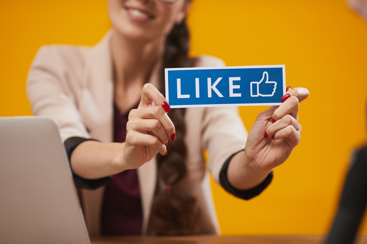 social media manager woman carries a like sign smiling because she knows social media myths