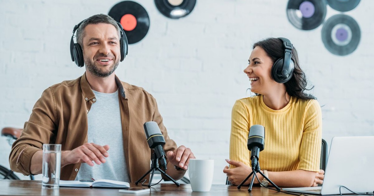 a man recording a podcast a woman looking at him and laughing podcast for digital marketing