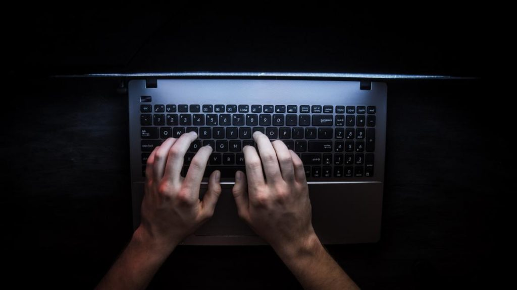 negative seo, hand and laptop
