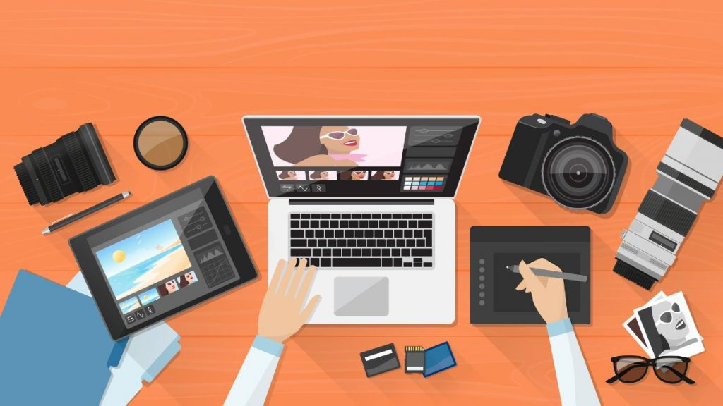 Professional photographer working at the office desk organizes her pictures using a laptop and a graphic tablet