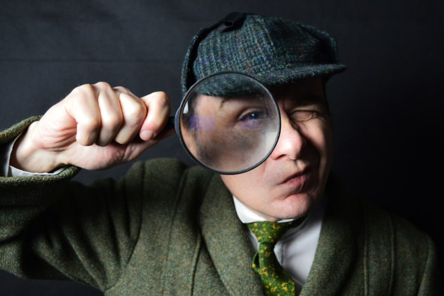 like sherlock holmes, a man is a magnifying glass in his hand